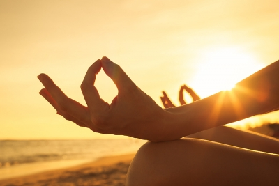 up-close photo of a woman's hands who is meditating on the beach